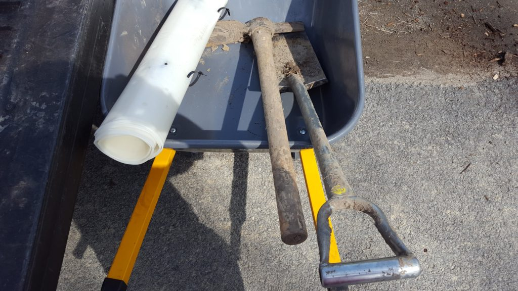 Tree tubes and muddy planting tools in wheel barrow